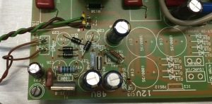 "48V regulator components, after careful examinaton, were ""kludge wired"" into holes of the existing PCB. 12V regulator was mounted near the transformer leaving 12V spot on main PCB empty."
